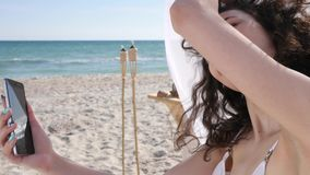 Woman taking selfi, smiling girl doing photo on mobile phone in beach, video from travel at summer season, female stock footage