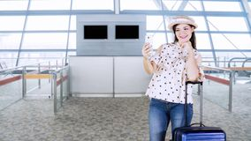 Woman taking selfie in airport terminal. Happy young woman taking selfie photo in the airport terminal with her suitcase and wearing a hat stock video footage