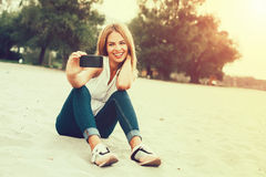 Woman taking selfie on the beach Royalty Free Stock Photo
