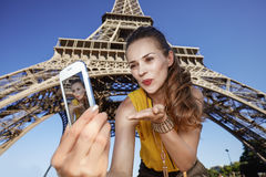 Woman taking selfie and blowing air kiss near Eiffel tower. Touristy, without doubt, but yet so fun. happy young woman taking selfie with smartphone and blowing Royalty Free Stock Images
