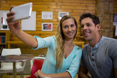 Woman taking selfie with boyfriend through mobile phone in cafe Royalty Free Stock Photo