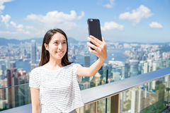 Woman taking selfie by cellphone in Hong Kong Stock Images
