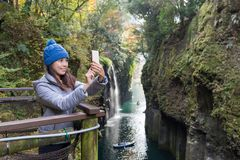 Woman taking selfie by cellphone in Takachiho gorge royalty free stock image