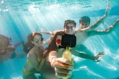 Group of young people taking selfie underwater. Woman taking selfie of friends with waterproof camera under the water in swimming pool. Group of young people Stock Image