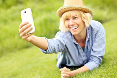 Woman taking selfie on the grass Stock Photography