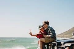 Making memories during their road trip. Woman taking selfie with her boyfriend at the beach. Couple standing by their car taking self portrait using a smartphone stock photos