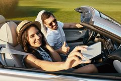 Woman taking selfie with her boyfriend on smartphone in the cabriolet stock photos