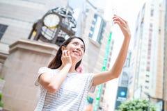 Woman taking selfie by mobile phone in Causeway bay of Hong Kong Royalty Free Stock Photos