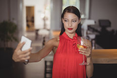 Woman taking selfie from mobile phone while having wine Stock Photography