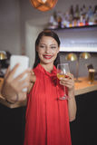 Woman taking selfie from mobile phone while having wine Stock Photos