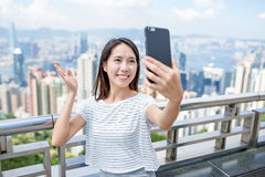 Woman taking selfie by mobile phone in Hong Kong Royalty Free Stock Photography