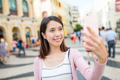 Woman taking selfie by mobile phone in Macao Stock Photography