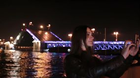 Woman taking selfie. A movable Palace Bridge St. Petersburg at the background. City illumination at night. Pretty young woman smiling, taking selfie at night. A stock video