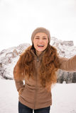 Woman taking selfie outdoors among snow-capped mountains Stock Photo