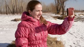 Woman taking selfie with a phone. Woman taking a selfie in a winter forest with a smartphone stock video footage