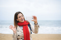 Woman taking selfie photo with smartphone and waving Stock Photo