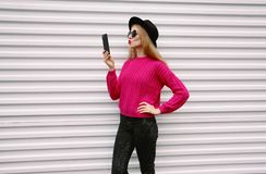 Woman taking selfie picture by smartphone blowing red lips sending sweet air kiss. Fashion, technology and people concept - woman taking selfie picture by stock image