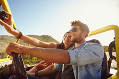 Woman taking selfie on road trip with man. Couple on road trip, men driving a buggy car and women taking selfie on her mobile phone royalty free stock photos