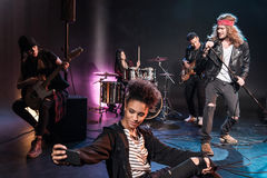 Woman taking selfie with rock and roll band performing concert on stage Stock Photography