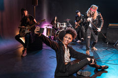 Woman taking selfie with rock and roll band performing concert on stage. Young women taking selfie with rock and roll band performing concert on stage Royalty Free Stock Images