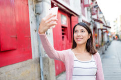 Woman taking selfie by smart phone in Rua da felicidade Royalty Free Stock Photography