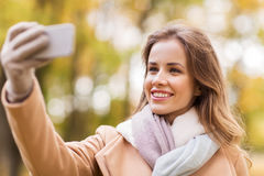 Woman taking selfie by smartphone in autumn park Stock Images