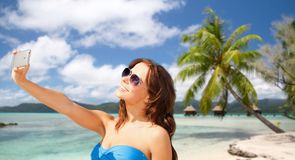 Woman taking selfie by smartphone on beach Stock Image