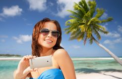 Woman taking selfie by smartphone on beach Royalty Free Stock Photo