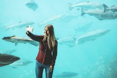 Woman taking selfie by smartphone at big aquarium Stock Photography