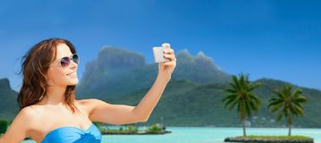 Woman taking selfie by smartphone on bora bora Royalty Free Stock Images