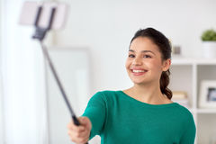 Woman taking selfie by smartphone monopod at home Stock Photography
