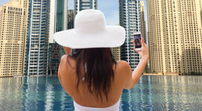 Woman taking selfie with smartphone over city pool Royalty Free Stock Photography
