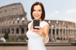 Woman taking selfie with smartphone over coliseum Royalty Free Stock Photos