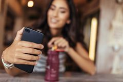 Woman taking a selfie for her blog. Woman taking a selfie with a smoothie placed on the table using a mobile phone for her food blog. Food blogger shooting Stock Image