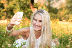 Woman taking a selfie in a summer park Stock Photography