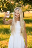 Woman taking a selfie in a summer park Stock Photos
