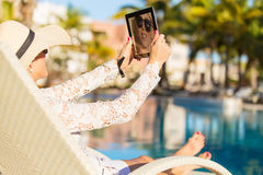 Woman taking selfie with tablet computer while enjoying vacation in tropical resort Royalty Free Stock Photo