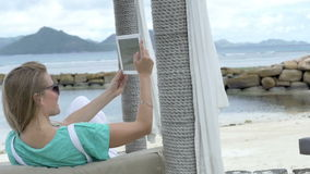 Woman taking selfie with tablet computer while enjoying vacation in tropical resort. Woman relaxing on luxury beach stock video