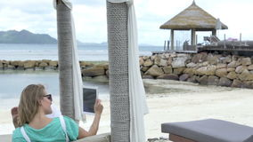 Woman taking selfie with tablet computer while enjoying vacation in tropical resort. Woman relaxing on luxury beach stock video footage