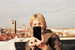 Woman taking a selfie on a terrace in Venice royalty free stock image