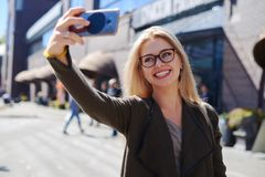 Woman taking selfie using mobile camera in city royalty free stock images