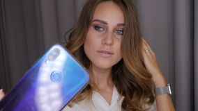 Woman taking a selfie. Young beautiful woman in white posing and taking a selfie on a smartphone. Blue-gray-eyed girl straightens her hair and photographs stock video footage