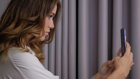 Woman taking a selfie. Young beautiful woman in white posing and taking a selfie on a smartphone. Cute girl photographs herself on the phone slow motion stock footage