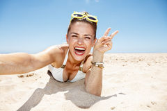 Free Woman Taking Selfies And Showing Victory Gesture At Sandy Beach Royalty Free Stock Photo - 69824855