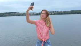 Woman taking selfies on her phone near lake in slow motion stock footage