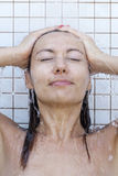 Woman taking a shower Stock Images