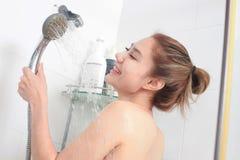 Woman taking a shower enjoying water splashing on her royalty free stock image