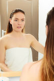 Woman after taking shower. Girl with wet hair looking in mirror. Bathroom hygiene stock photos