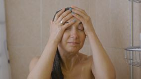 Woman taking a shower. Portrait of young smiling caucasian woman with closed eyes standing under the shower rinsing the. Hair on her head stock video footage
