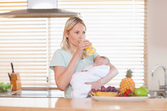 Woman taking a sip of juice while holding her baby Stock Photos